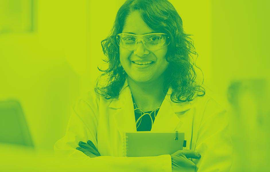 A female scientist holding a notebook and smiling directly at the camera