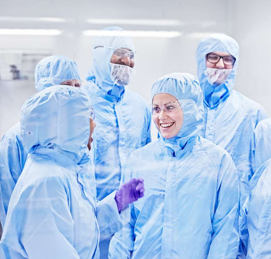 Group of scientists in the lab in full Tyvek suits smiling and talking