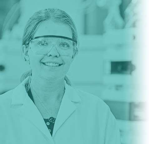 A scientist with blonde hair and goggles on looking at the camera with a turquoise wash over the photo.