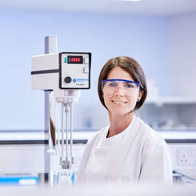 Woman in lab goggles standing in front of a Silverson mixer