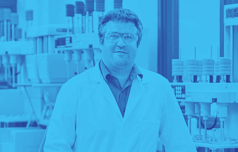 A male scientist in the lab looking at the camera with a blue wash over the photo