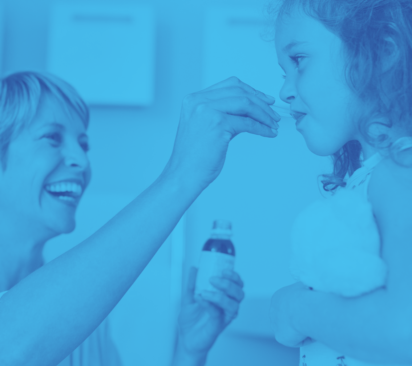 Older woman giving child liquid oral medication with a spoon