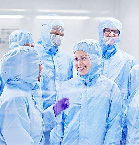 A group of scientists in full Tyvek suits in one of the labs at Quotient Sciences
