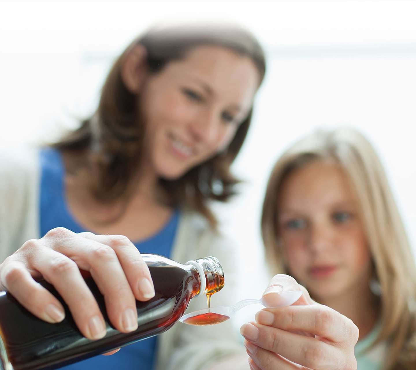 A woman pouring some liquid medication into a spoon about to give it to a child